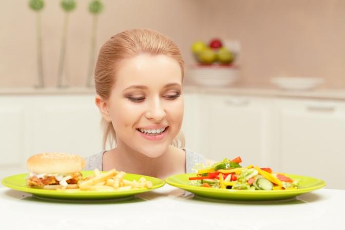 Eine Frau sieht auf ein Teller mit gesundem und ein Teller mit ungesundem Essen