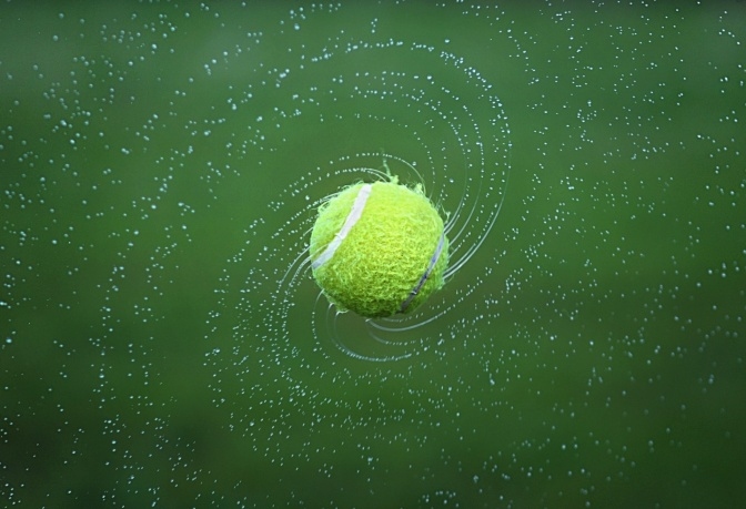 Ein Tennisball spritzt Wasser von sich
