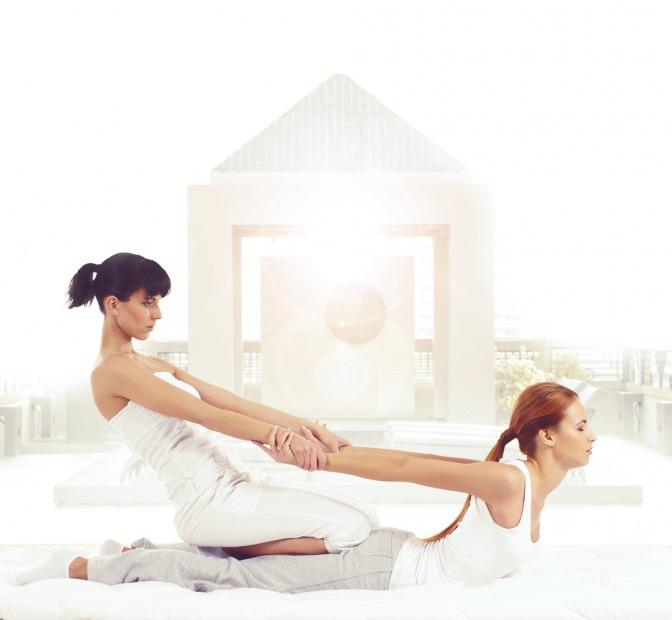 Zwei Frauen führen eine Thai Massage durch