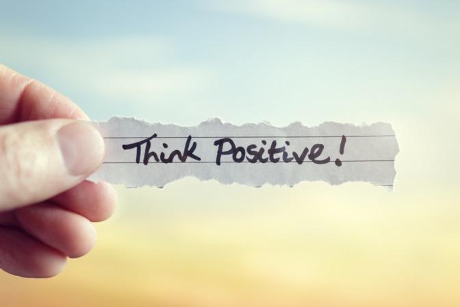 Ein Zettel mit der Aufschrift Think positive ist zu sehen