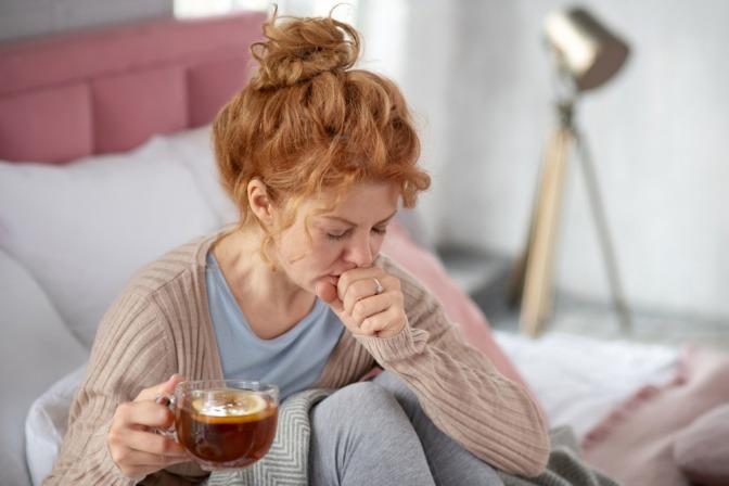 Frau beim Husten und Tee mit Thymian