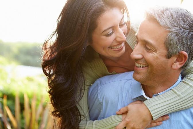 Tipps für eine glückliche Beziehung braucht das Paar auf diesem Foto nicht unbedingt. Beim Sonnenuntergang trägt ein Mann seine Frau Huckepack auf dem Rücken, während sie gemeinsam über einen kleinen Hügel laufen.