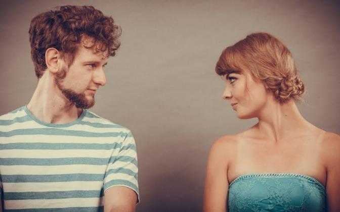 Ein Paar steht nebeneinander, beide haben den Kopf um jeweils 90 Grad gedreht und blicken sich herausfordernd an.