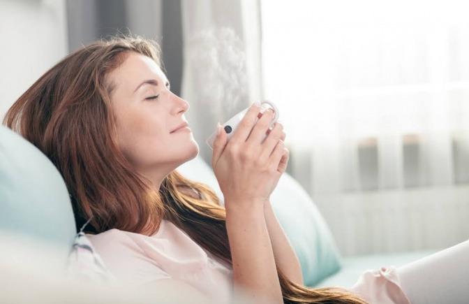 Eine Frau sitzt mit geschlossenen Augen auf einem Sofa, hält eine Tasse Tee in der Hand und wirkt sehr entspannt.
