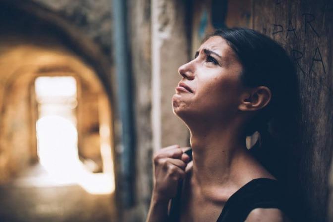 Eine Frau steht in einem Tunnelgewölbe mit dem Rücken an eine Wand gelehnt; sie wirkt verzweifelt und nervös.