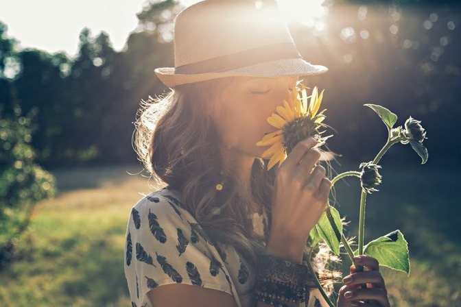 Eine Frau riecht an einer Blume.