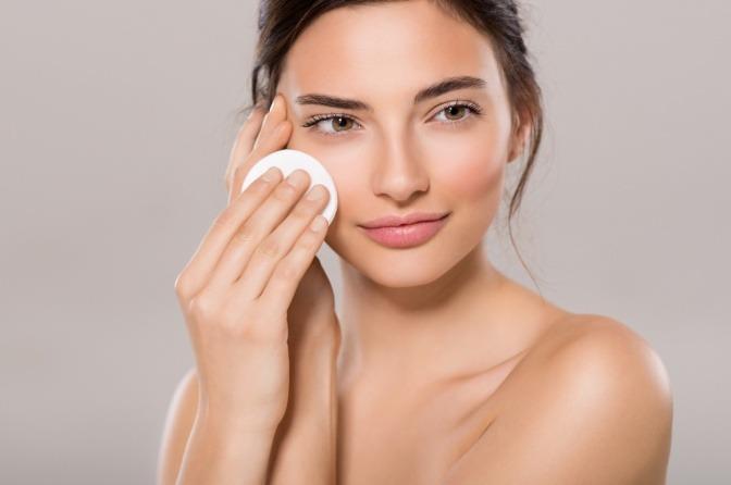 Eine Frau reinigt ihr Gesicht