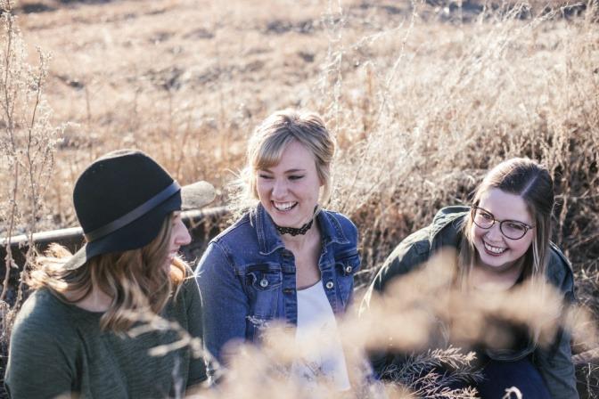 Drei Freundinnen sitzen an einem sonnigen Tag auf einer Bank vor einem Gerstenfeld.