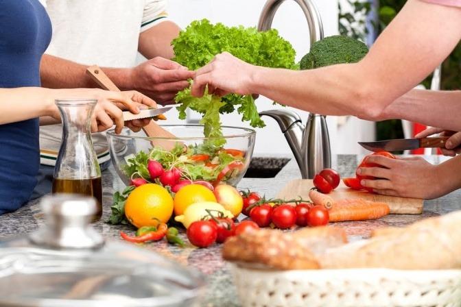 Mehrere Menschen kochen gemeinsam in einer Küche.