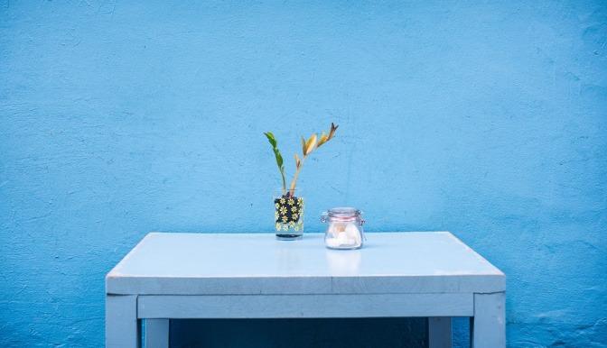 Ein blauer Tisch steht vor einer blauen Wand