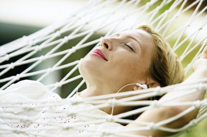 Eine Frau liegt in einer Hängematte und hört genussvoll Musik.