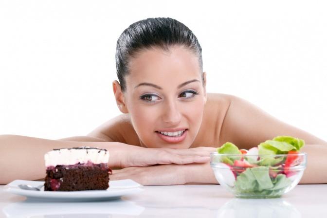 Vor einer Frau stehen ein Stück Torte und eine Schüssel Salat