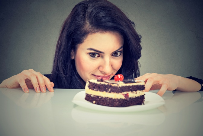 Frau versucht dem Hunger auf Kuchen zu widerstehen