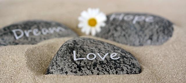 Steine liegen im Sand, darauf steht Dream, Love, Hope