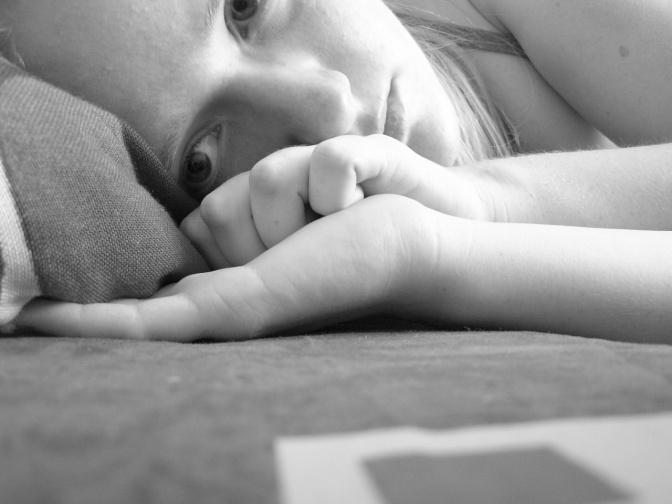 Eine Frau liegt traurig am Sofa
