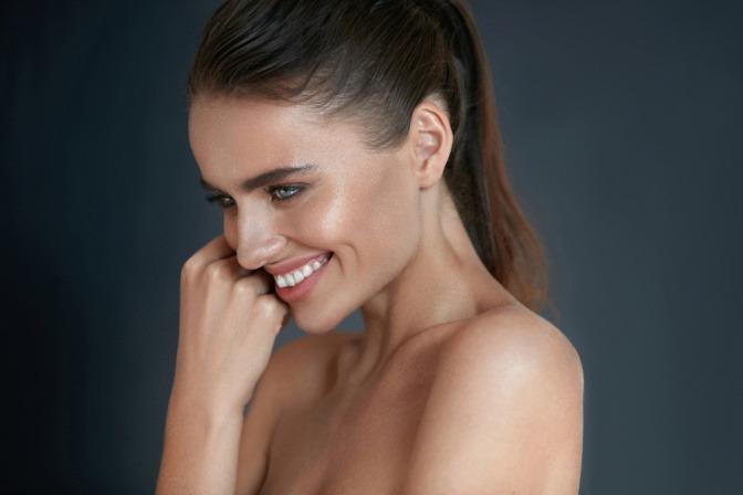 Eine Frau mit glänzender Haut lächelt