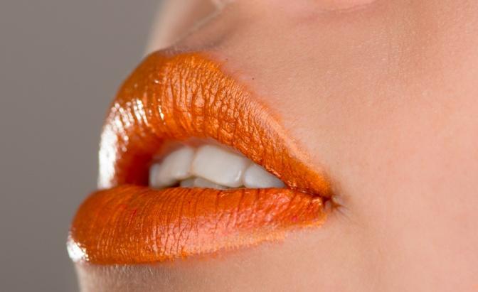 Eine orange geschminkte Lippe