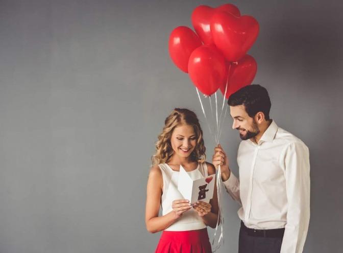 Ein Mann macht einer Frau während eines Dates ein Geschenk, das aus mehreren roten Luftballons und einer romantischen Karte besteht.