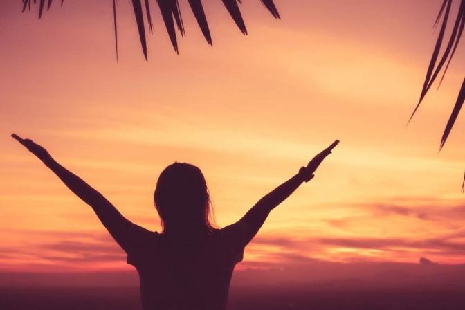 Eine Frau streckt während des Sonnenuntergangs bei einem rot gefärbten Himmel ihre Arme in die Höhe.