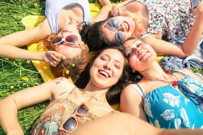 Vier Freundinnen liegen an einem sonnigen Tag auf einer Wiese.