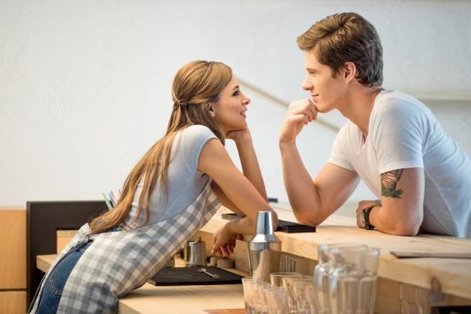 Ein Mann und eine Frau flirten über eine Theke hinweg.