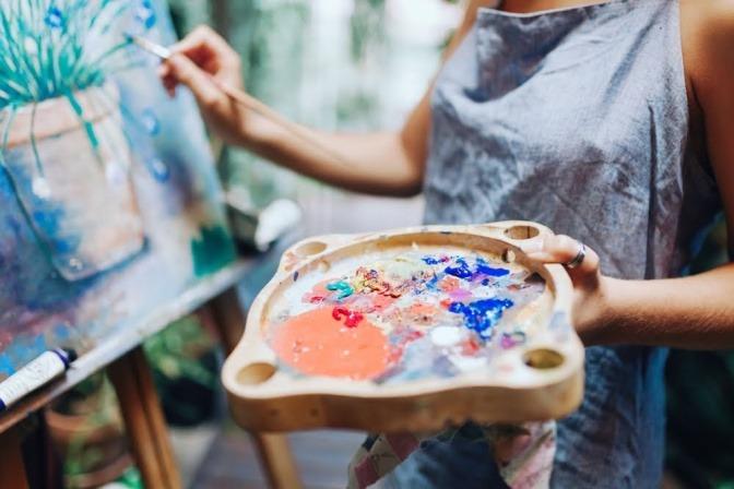Eine Frau steht an einer Staffelei und malt.