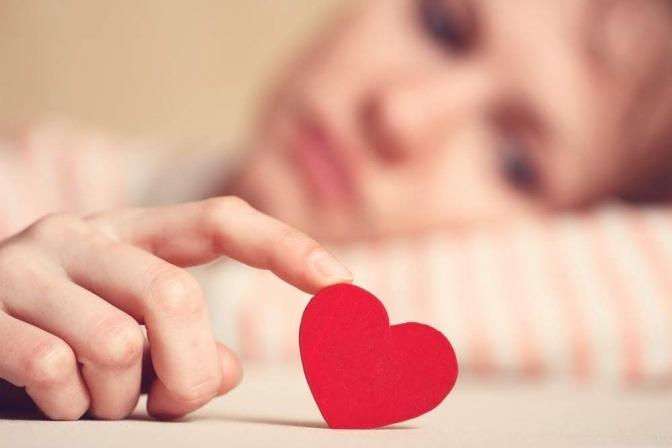 Eine traurige Frau spielt mit einer Holzfigur in der Form eines kleinen roten Herzens.