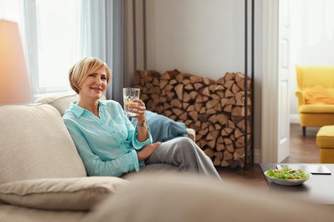 Frau in den Wechseljahren hält ein Glas Wasser für schöne Haut