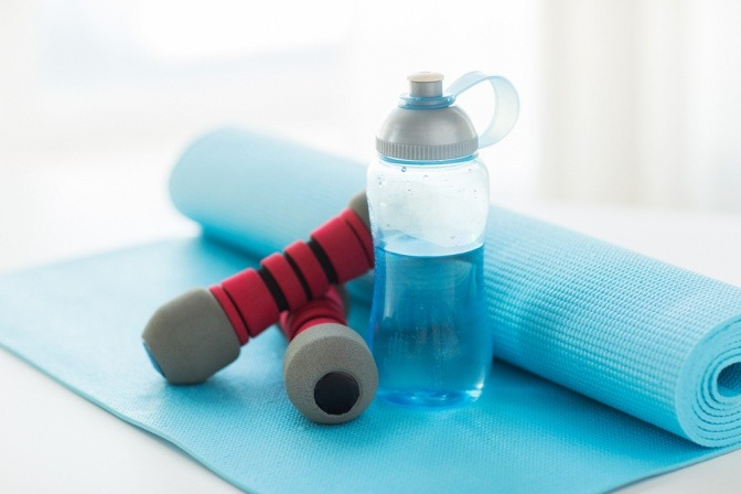 Eine Trinkflasche steht auf einer Sportmatte, daneben liegt eine Hantel