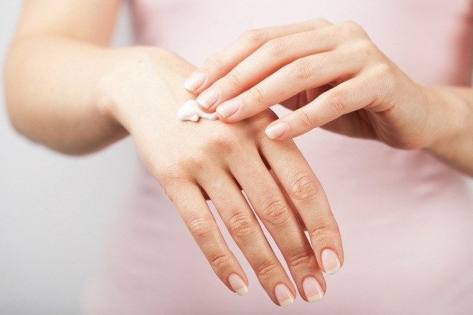 Eine Frau cremet ihre trockene Haut an den Händen ein