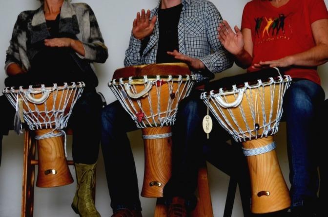 Menschen trommeln bei einem Trommelworkshop