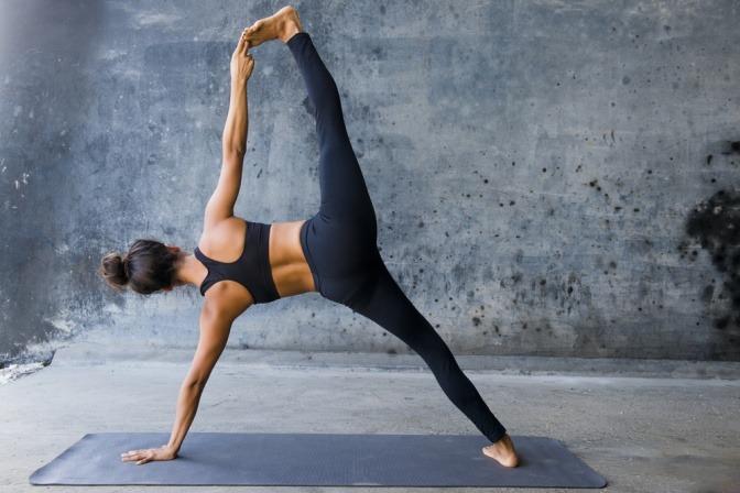 Eine Frau führt eine der Bewegungsübungen (Asanas) aus