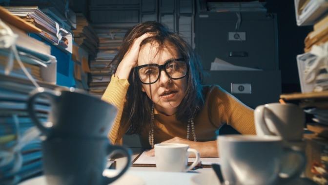 Gestresste und erschöpfte Frau, die am Schreibtisch sitzt.
