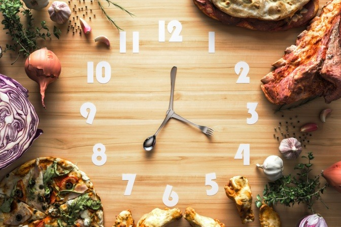 Eine Uhr mit Zeigern aus Besteck und Lebensmittel zeigen die Zeit