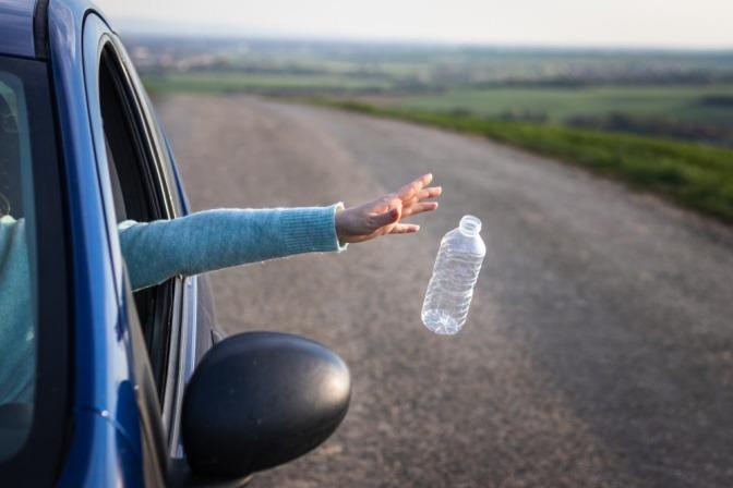 Jemand schmeißt beim Autofahren eine Plastikflasche aus dem Fenster.