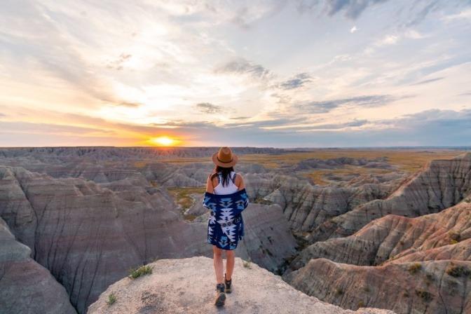 Ein Mädchen mit Hut auf dem Gipfel eines Hügels bewundert in Stille und Einsamkeit eine friedliche Naturlandschaft.