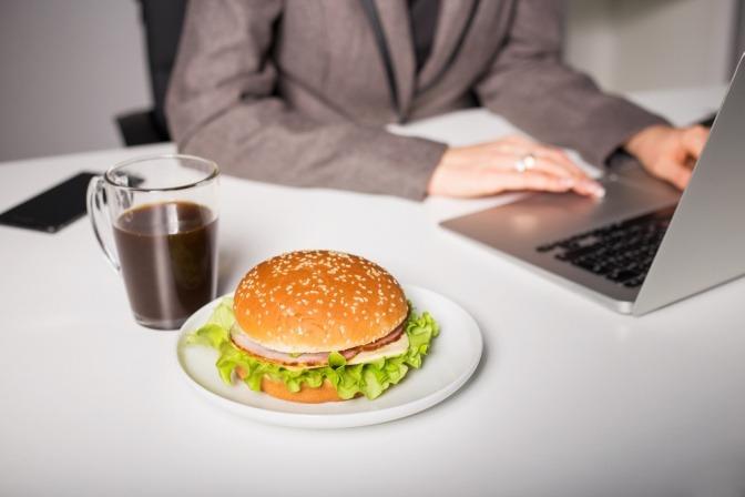 Ein Burger liegt neben einem Laptop