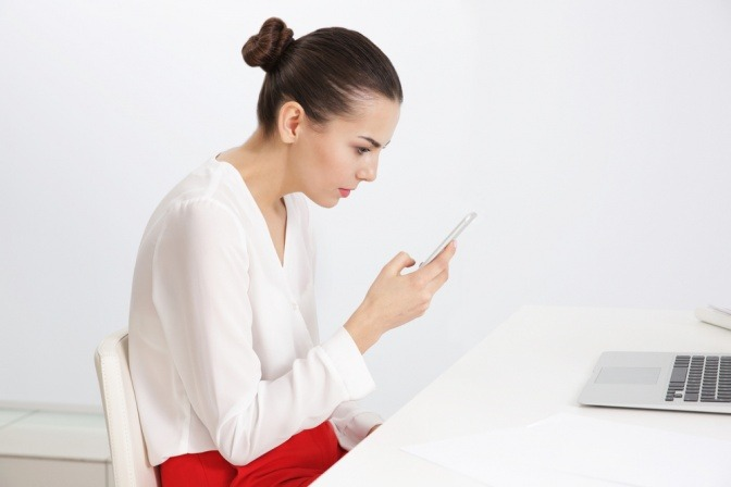 Frau am Schreibtisch vor Smartphone und Computer.
