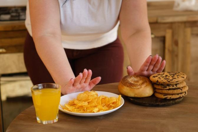 Frau schiebt ungesundes Essen weg.