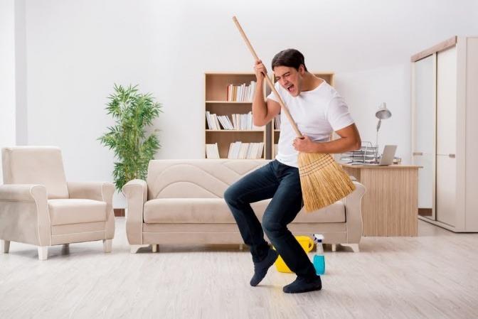 Ein junger Mann räumt mit viel Enthusiasmus seine Wohnung auf und funktioniert einen Besen dabei zur Luftgitarre um.