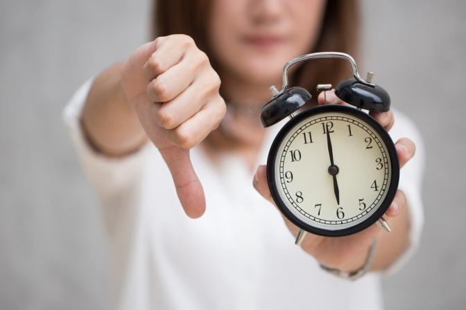 Frau mit Uhr und Daumen nach unten als Symbol für Unpünktlichkeit