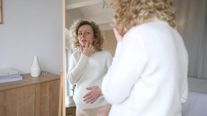 Schwangere Frau ohne unreine Haut vor dem Spiegel