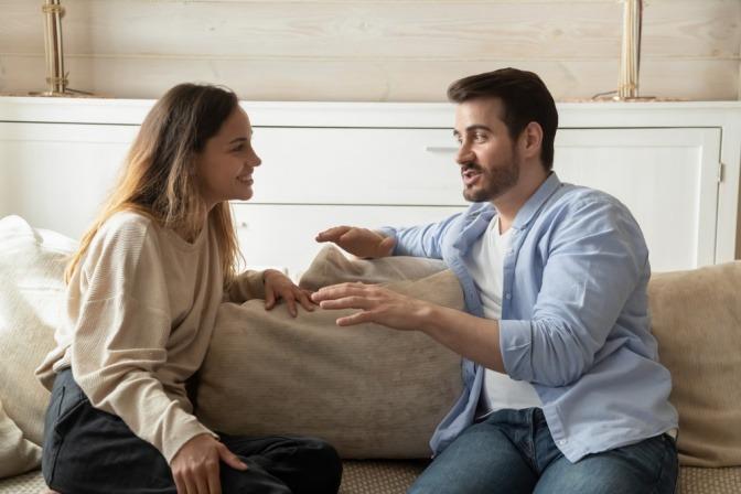 Frau und Mann unterhalten sich angeregt auf Sofa.