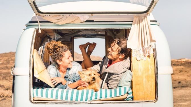 Ein junges Paar liegt zusammen mit seinem Hund auf der Schlafbank eines Campingmobils.