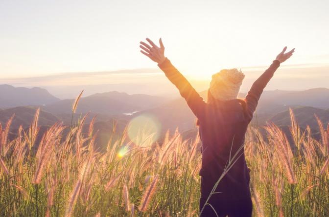 Frau steht in der Natur und hebt beide Arme in die Höhe