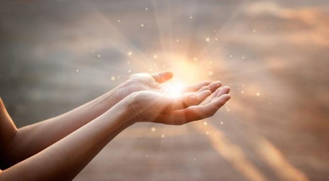 In Händen einer Frau leuchtet Licht als Zeichen für Seelen