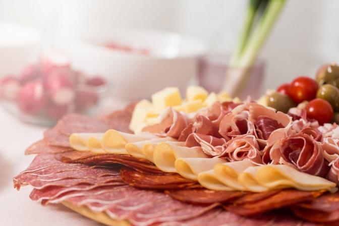 Verbotene Lebensmittel bei Rheuma (Wurst und fetter Käse) sind angerichtet