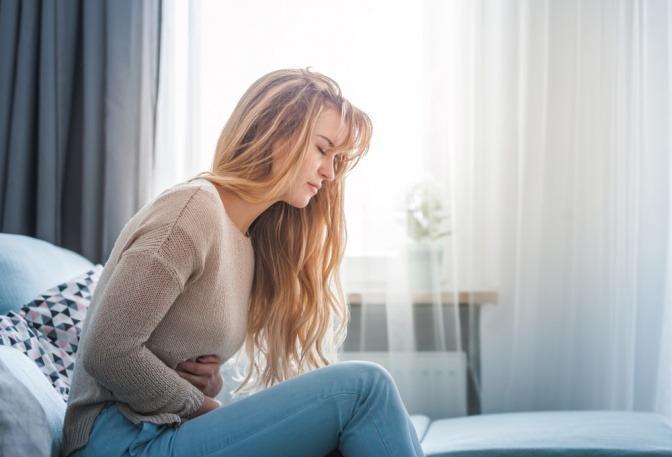 Eine Frau greift auf ihren Bauch wegen Verdauungsproblemen