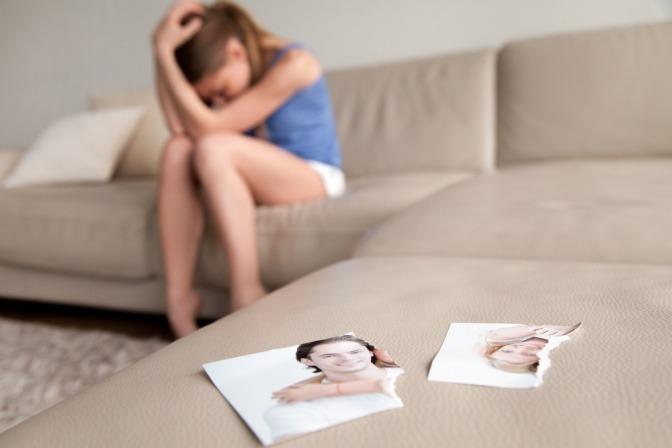Mit der Vergangenheit abschließen - ein in zwei Teile zerrissenes Foto eines Paars, das im Vordergrund auf einer Couch liegt, während eine traurige Frau im Hintergrund sitzt und weint.