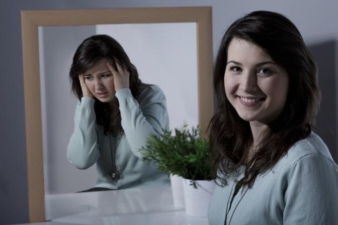 Eine lächelnde Frau im Vordergrund, ihr Spiegelbild dahinter zeigt eine verzweifelte und ängstliche Frau.